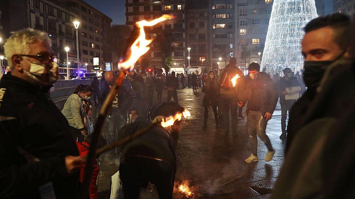 Sobre estas líneas, los manifestantes encienden sus antorchas, ayer, en Gijón. En el círculo, algunas de las pancartas exhibidas.   Juan Plaza