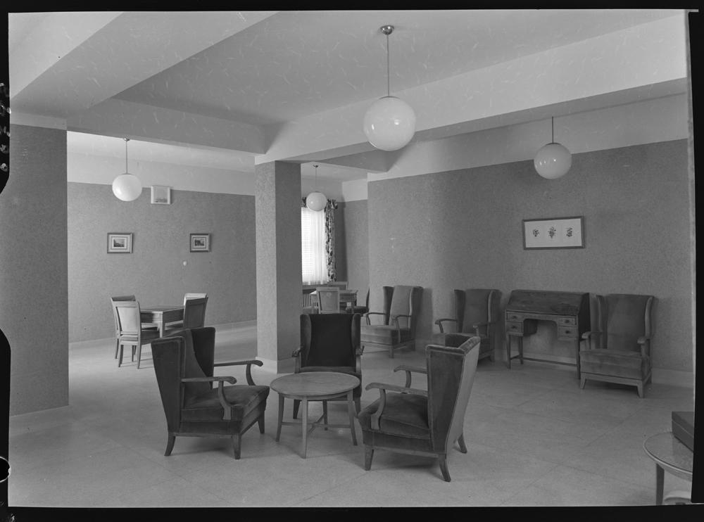 Interior de una sala de espera con mobiliario de madera y l�mparas que penden del techo con globo de cristal].jpg