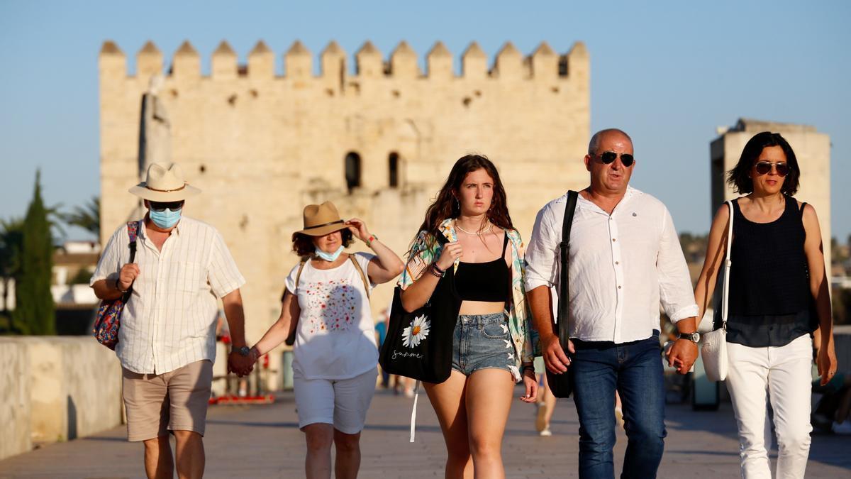 Turistas paseando por Córdoba, algunos sin mascarillas al haber distancia de seguridad.