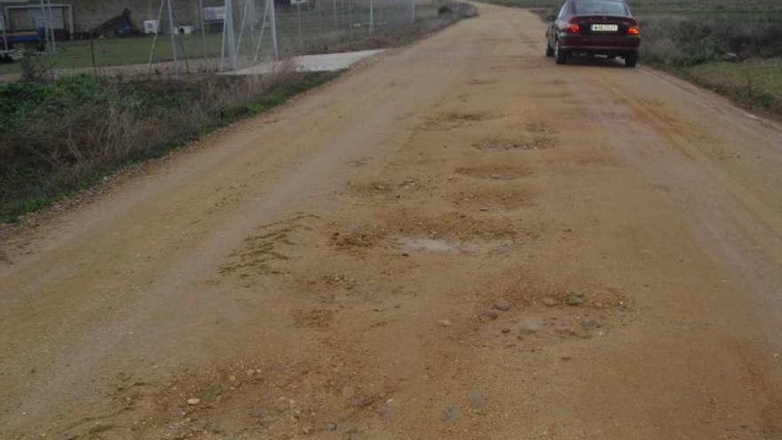 Un vehículo sortea los baches del camino de acceso al campo de fútbol de Tagarabuena.