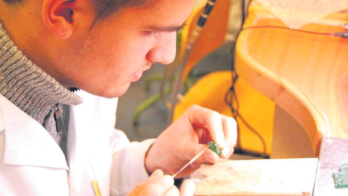 Un joven trabaja una pieza en la Escuela de Joyería.