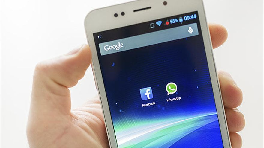 El logo de WhatsApp en un móvil junto a de Facebook.