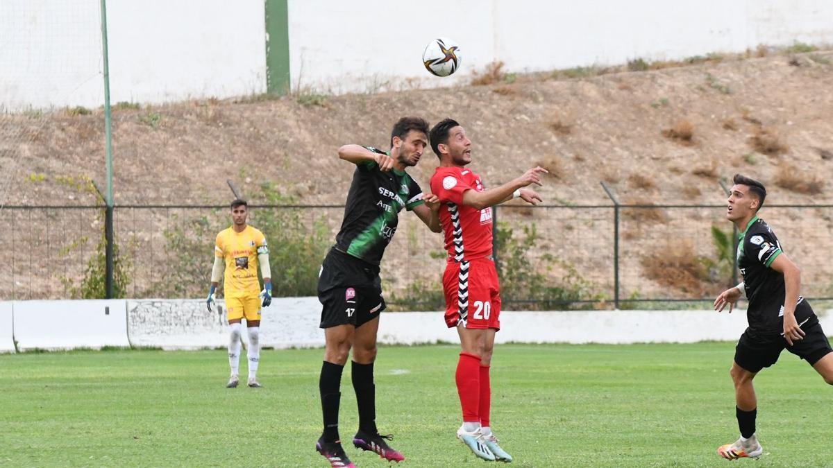 El rojiblanco Ezequiel salta junto a un jugador del Antequera en la disputa del balón.