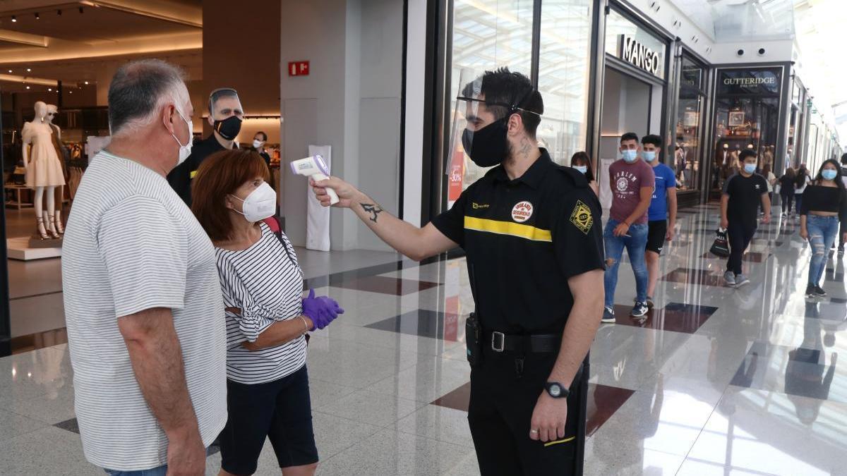 Un vigilante toma la temperatura a una ap`reja en un centro comercial.