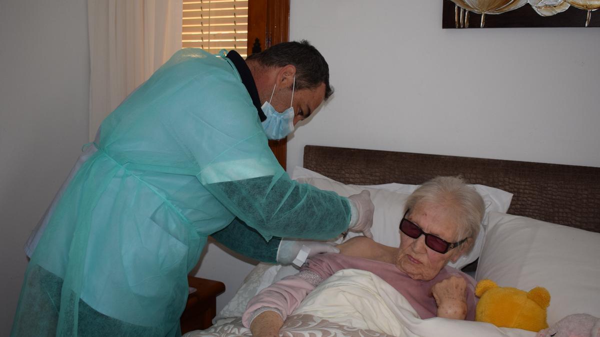 El facultativo inyecta la dosis a una vecina de avanzada edad