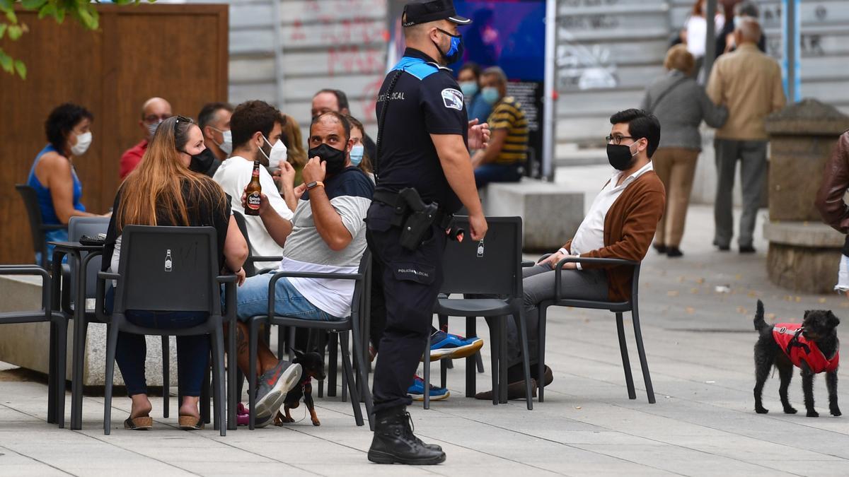 Un agente municipal junto a la terraza de un establecimiento hostelero en A Coruña.