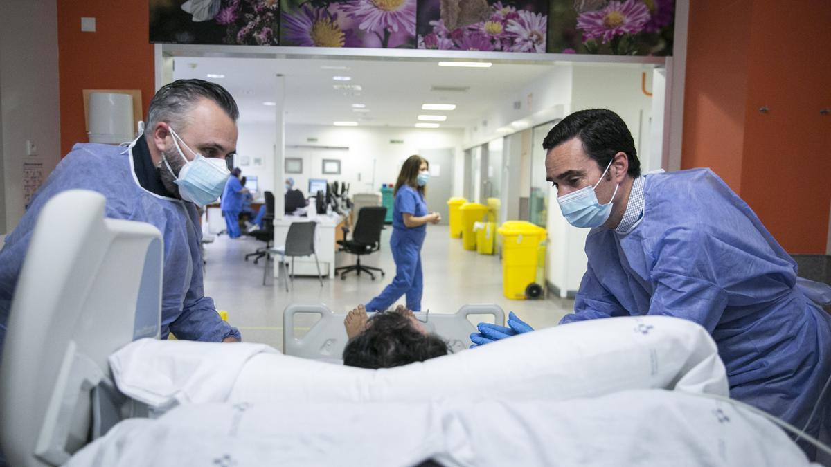 Dos sanitarios atienden a una paciente.