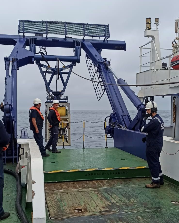 """Tres tripulantes del """"Ángeles Alvariño"""", bajando el robot submarino."""