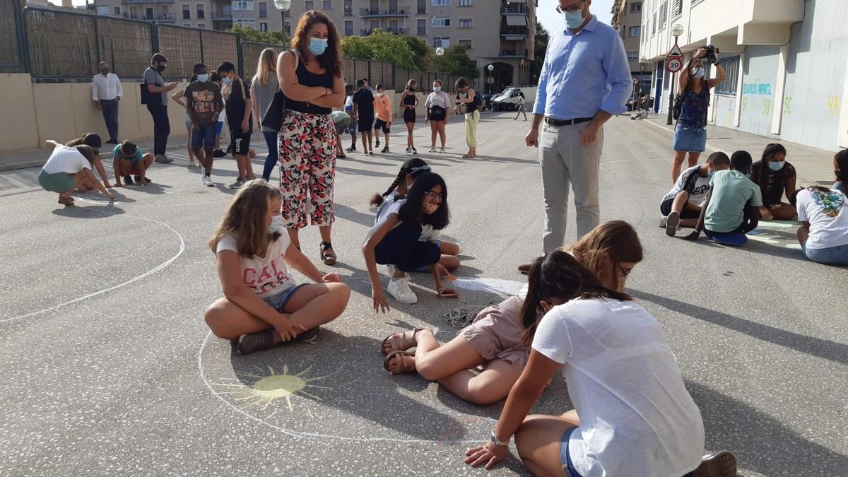 Hila y Pastor contemplan uno de los dibujos de los escolares en la calle.