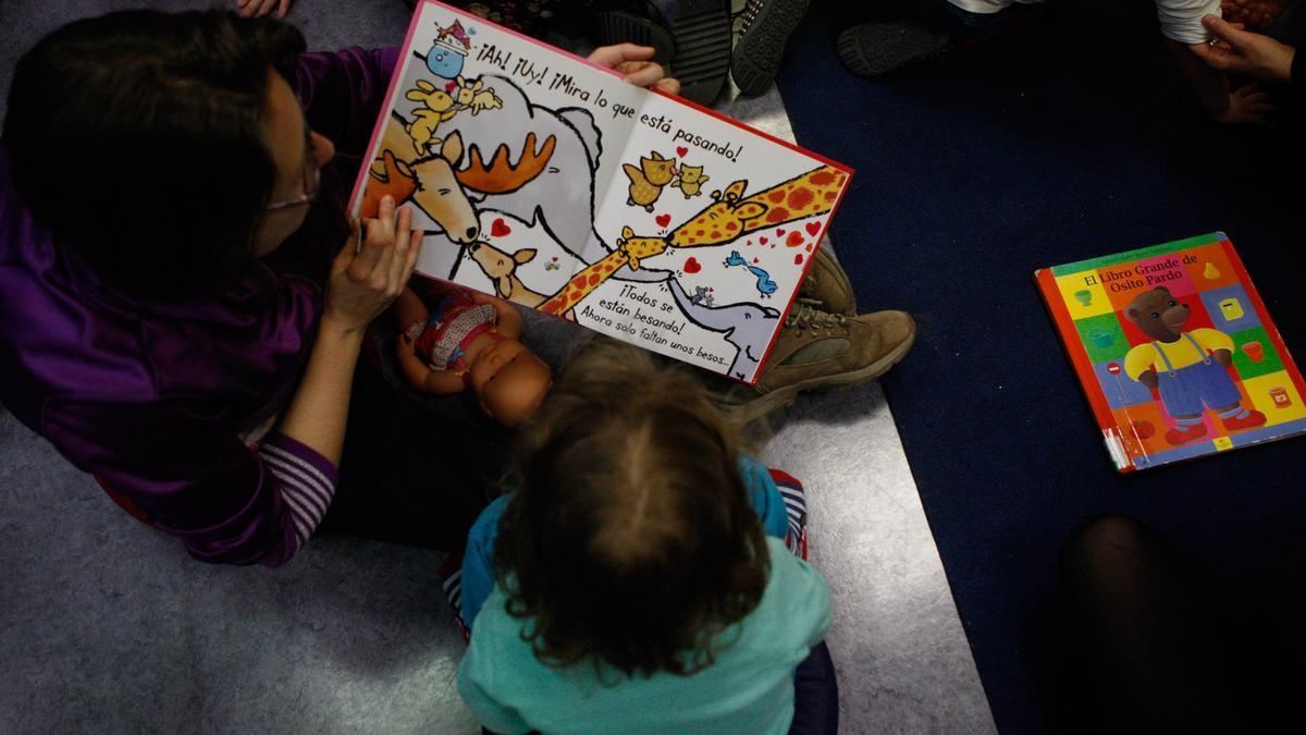 Una mujer lee un libro a una niña.