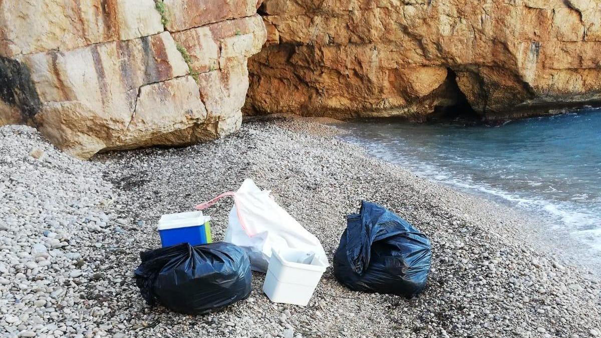 Neveras, una sombrilla, parrillas, vidrios y plásticos: la basura que dejan los bañistas en la cala dels Testos