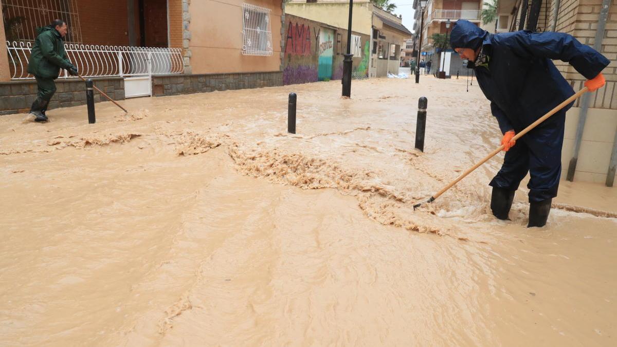 Dos vecinos tratan de controlar la corriente del agua durante las inundaciones de Los Alcázares en marzo de este año.