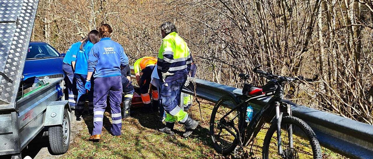 Los sanitarios atienden al herido, junto a su bicicleta, en el lugar del accidente.   SEPA