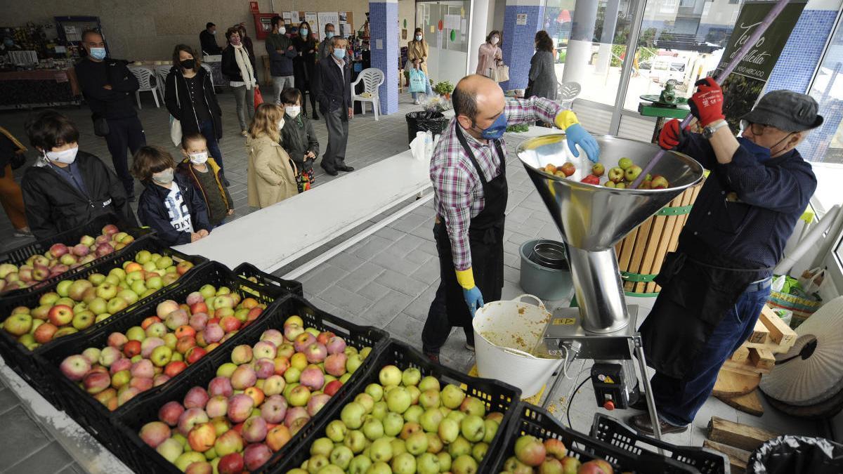 Víctor y Daniel Peroja, esta mañana en el Novo Mercado de A Estrada, elaborando en vivo mosto de manzanas recién cosechadas. // Bernabé / Javier Lalín