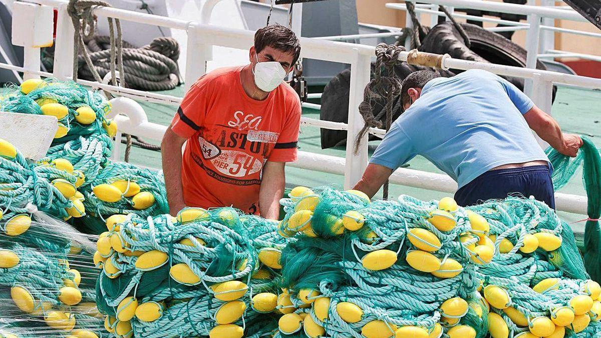 Pescadores con mascarillas preparan las redes para salir a faenar, ayer, en el puerto de Burela.