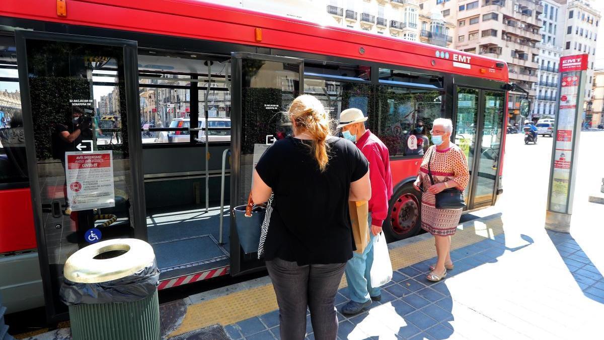 Usuarios de los autobuses de la EMT València esperan para acceder por la puerta del medio, como marca el protocolo covid.