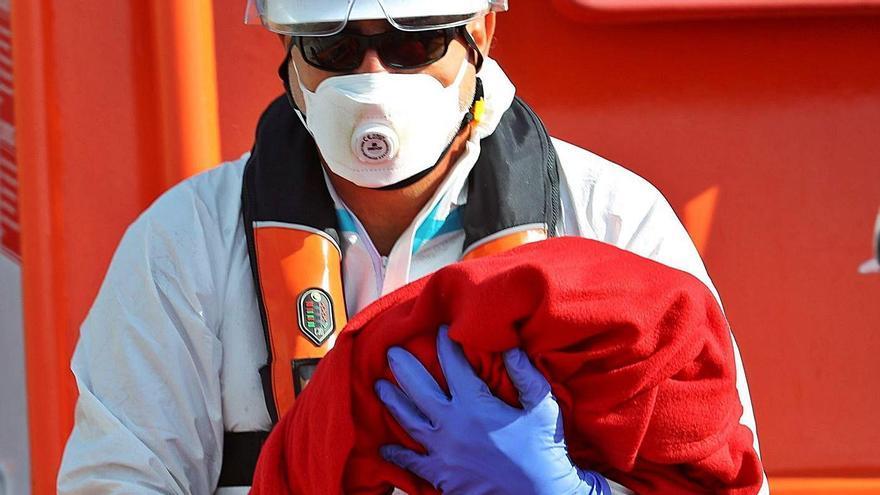 La niña nacida a bordo de la patera, en brazos de uno de los miembros de Salvamento Marítimo.