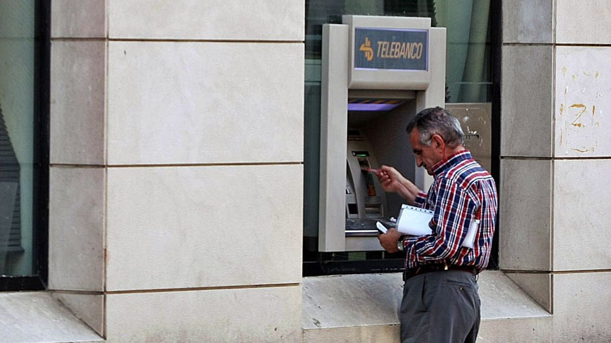Un hombre saca dinero de un cajero automático. | ÁLEX ZEA