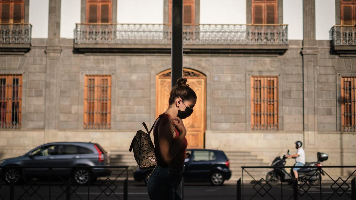 Una chica con mascarilla para protegerse del coronavirus pasea por Santa Cruz.
