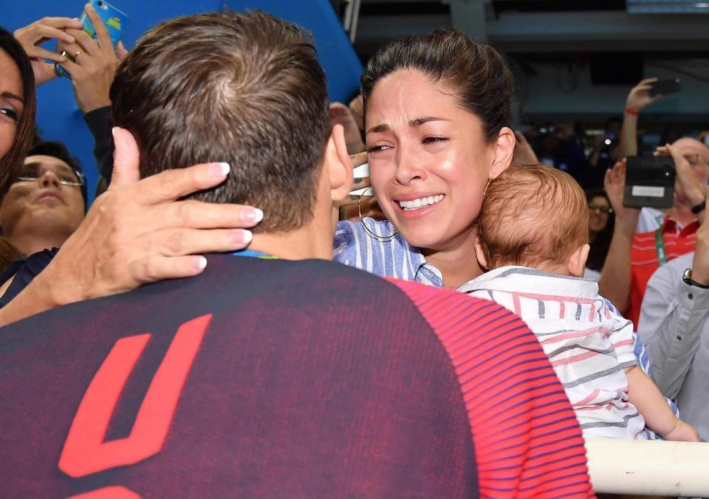 Michael Phelps saludando a su mujer y a su hijo.