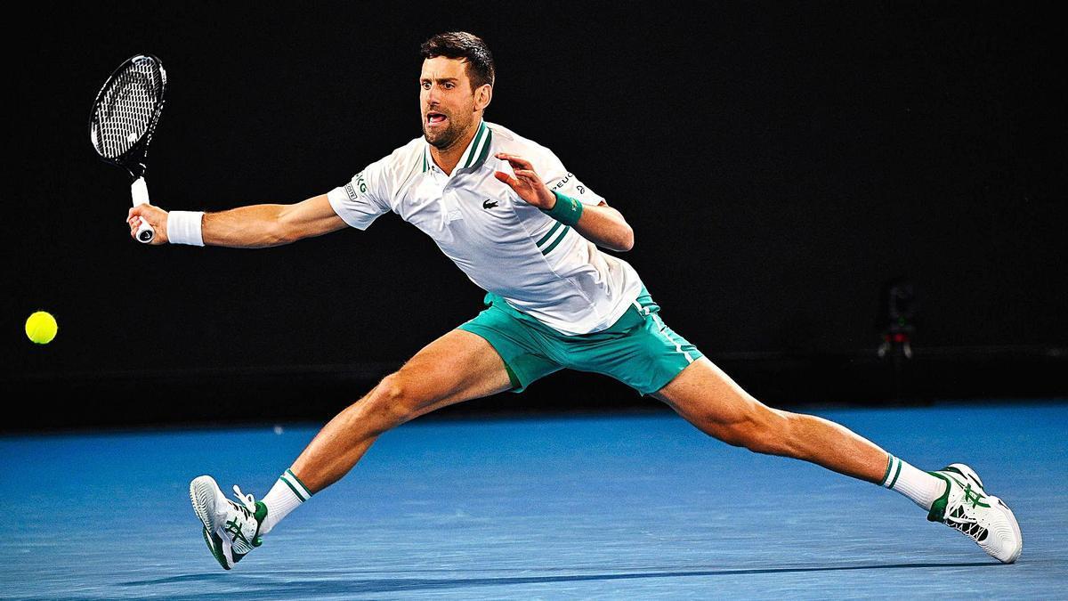 Djokovic devuelve la bola durante su partido ante Raonic, en Melbourne Park. |  // DEAN LEWINS