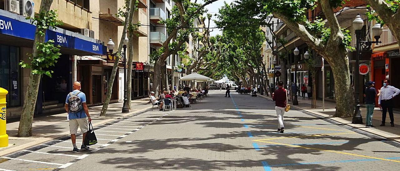 La calle Marqués de Campo de Dénia, con mesas y sillas de los negocios de hostelería. Dos señales prohiben el paso de vehiculos en el Primer Muntanyar de Xàbia | CARLOS LÓPEZ