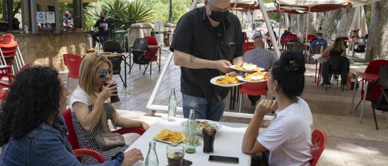 Un camarero atiende a tres clientas en un bar de Xàtiva.   PERALES IBORRA