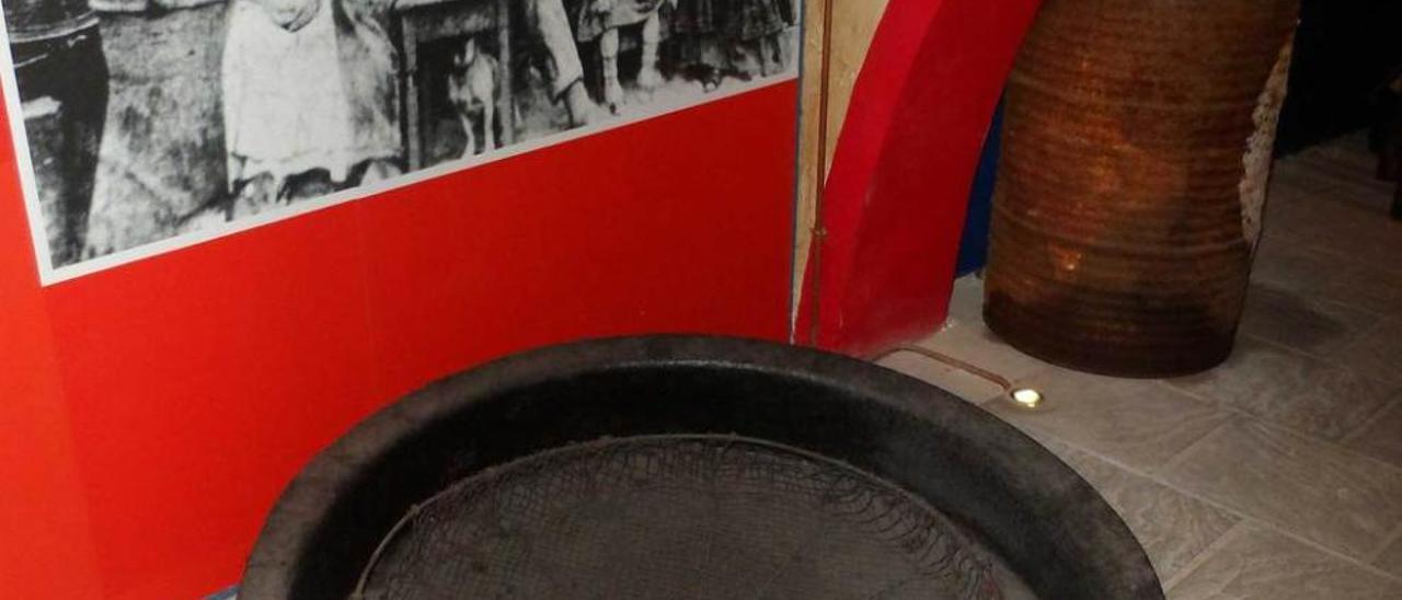 A la izquierda, una sartén antigua donde se pasaba el pescado antes de meterlo en la lata. A la derecha, una máquina y un carro en la exposición.