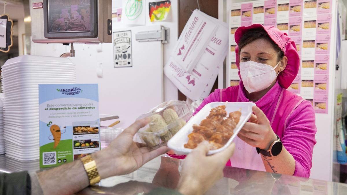 Jessica Plaza, de la pollería Marina, en el mercado de Hernán Cortés, entrega un lote a un usuario de la 'app'.
