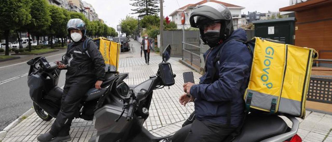 Dos repartidores de Glovo delante del McDonald's de Gran Vía en Vigo.     // PABLO HERNÁNDEZ GAMARRA