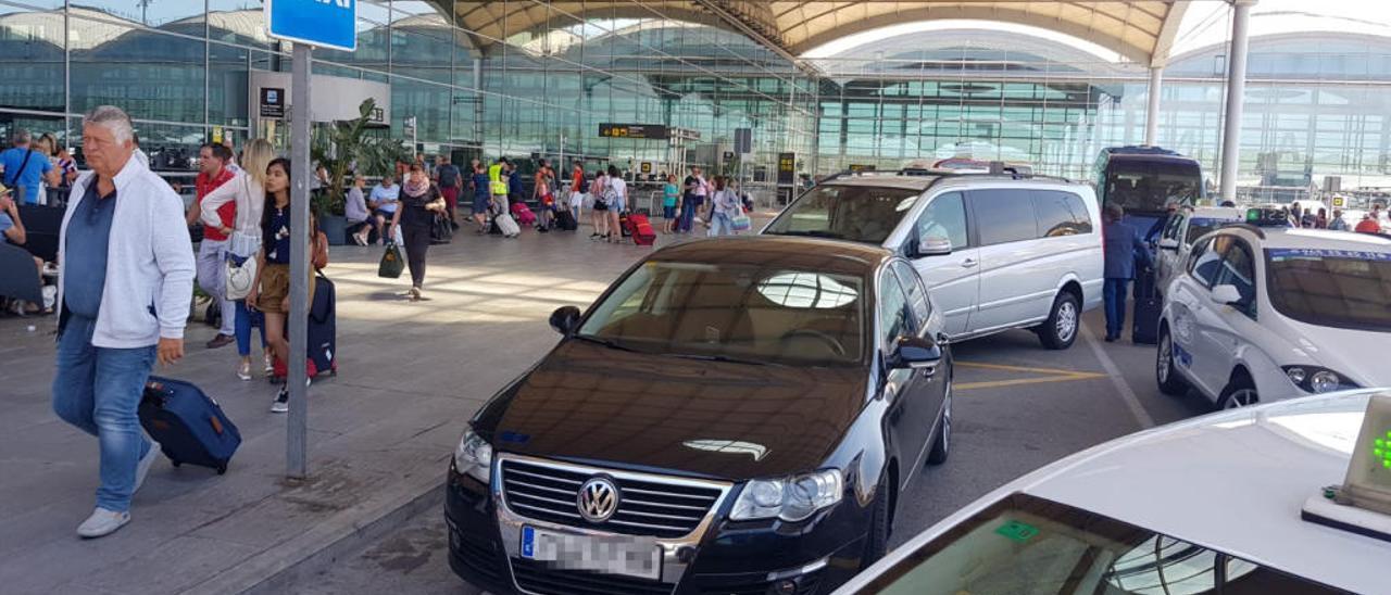 La parada de taxis del aeropuerto, con varios vehículos estacionados.