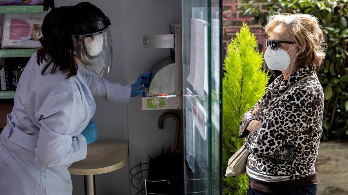 Una mujer recoge su mascarilla en una farmacia de Madrid.