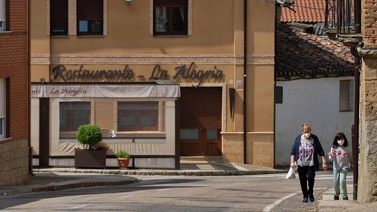 Una mujer y una niña caminan por las calles de Fuentes de Ropel. |
