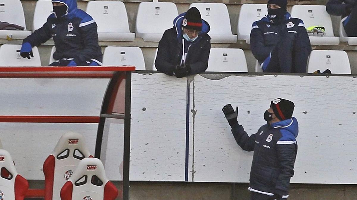 Fernando Vázquez, en el centro apoyado en la valla, conversa con David Sánchez.    // LOF