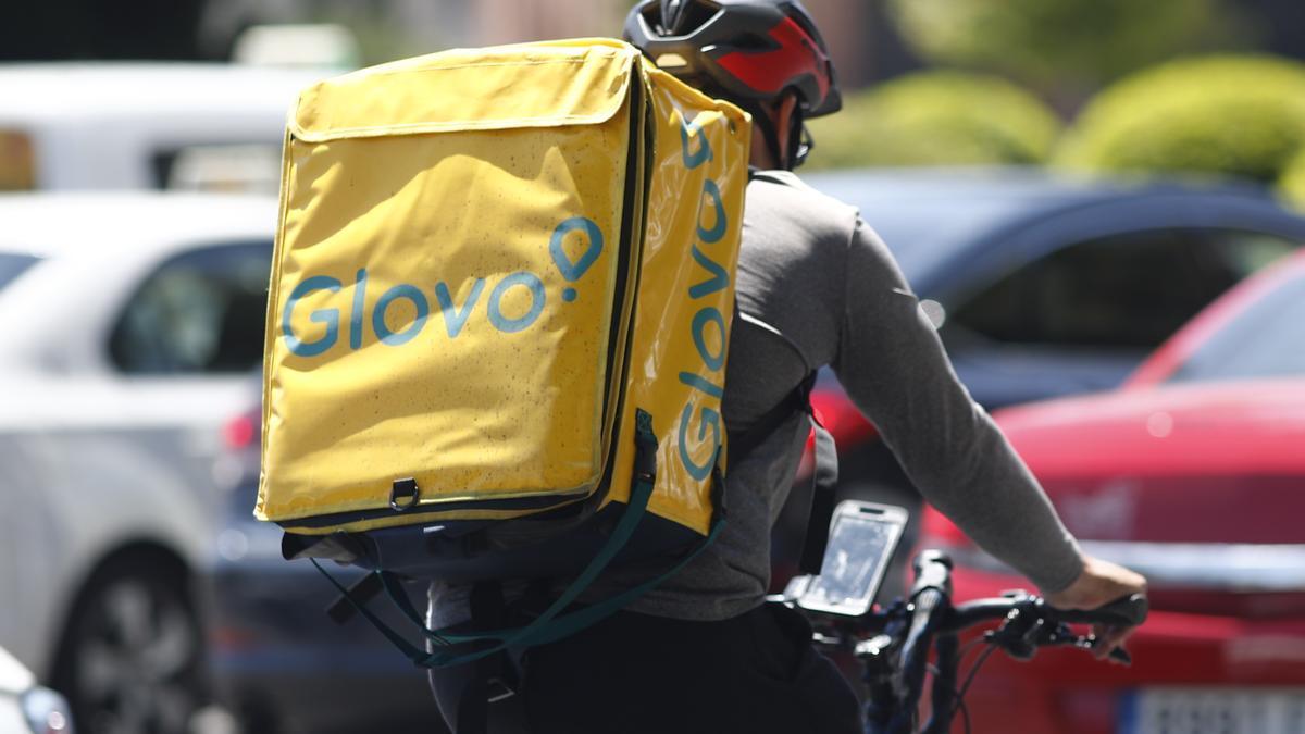 Un 'rider' de Glovo, circula en su bicicleta por una calle de Madrid.