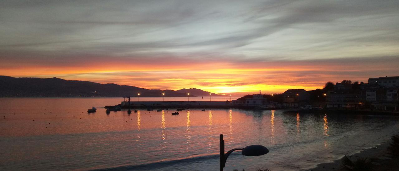 Puesta de sol en el puerto de Panxón, con cabo Silleiro al fondo
