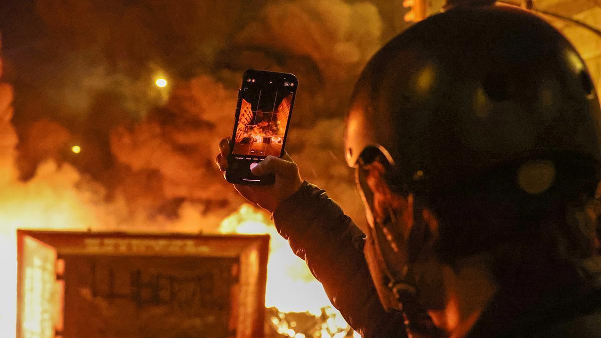 Un hombre saca una foto en los altercados de Barcelona.