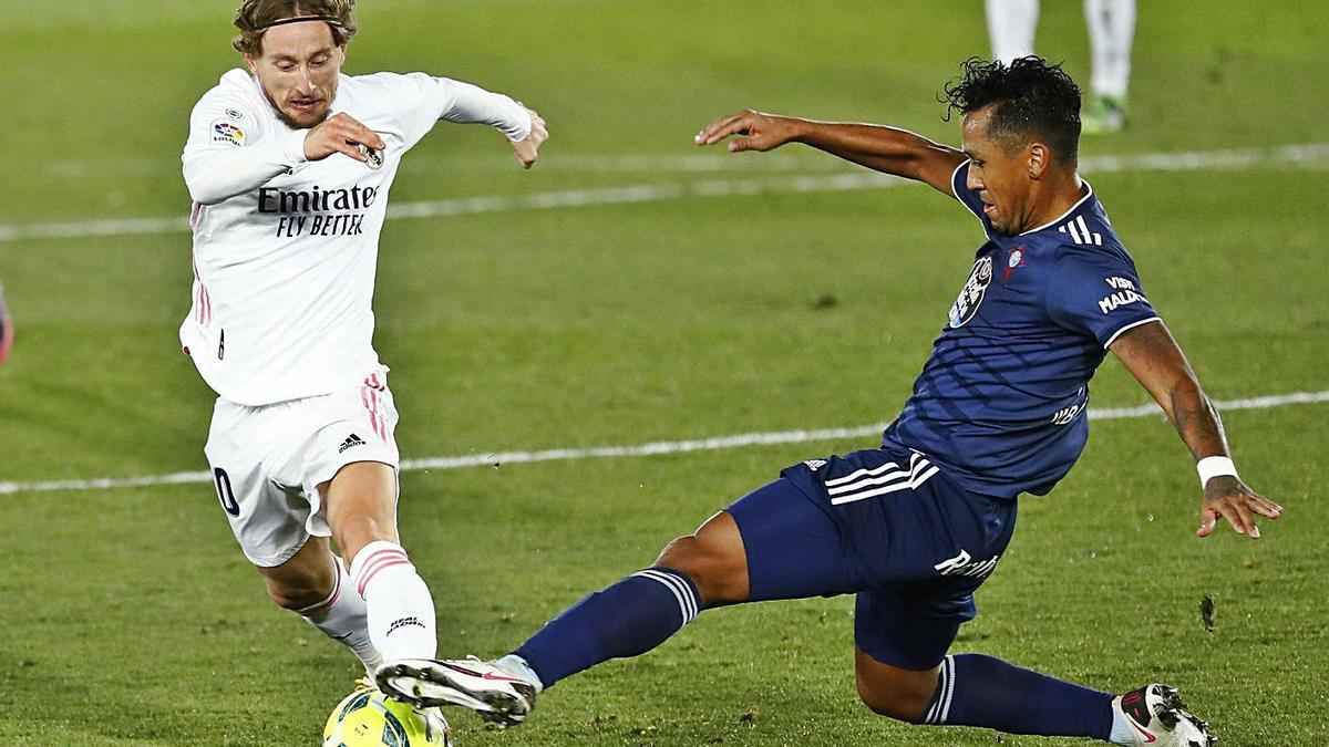 Luka Modric trata de recortar ante la entrada de Renato Tapia. | Reuters