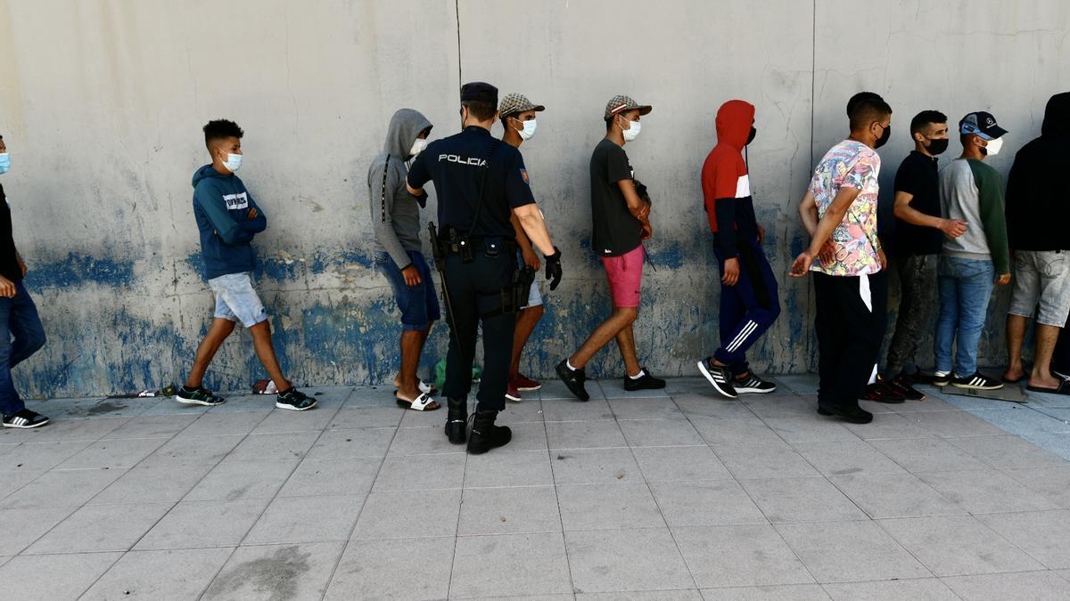 Varios migrantes hacen cola en el puesto fronterizo de Ceuta