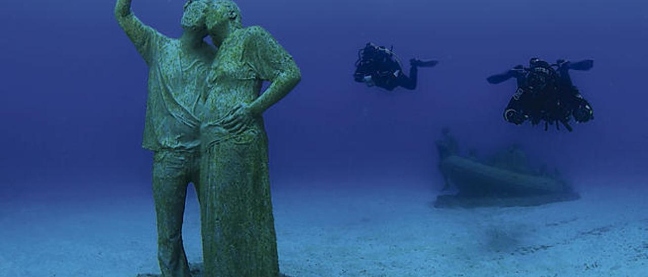 Una pareja haciéndose un selfie con un teléfono móvil con La balsa de Lampedusa a sus espaldas es la siguiente parada
