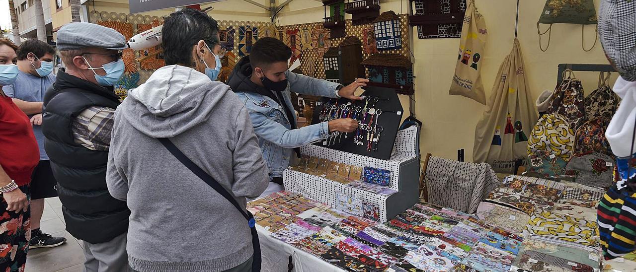 Varios ciudananos observan los artículos de un puesto de artesanía en la Feria de Navidad, el pasado domingo, en la avenida de Canarias, en Vecindario.