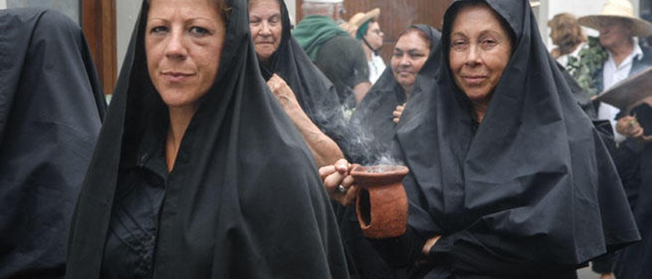 Las mujeres con la mantilla negra, y expandiendo el incienso.