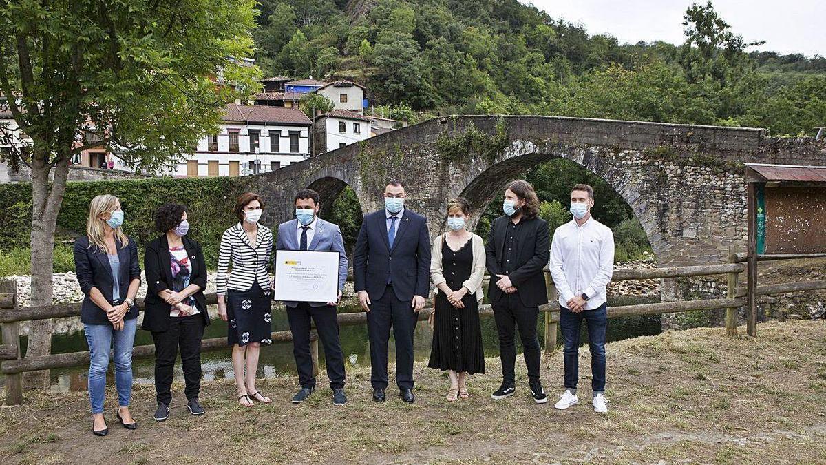 Julio García sostiene el diploma entre Isabel Oliver y Adrián Barbón junto a representantes regionales y locales, en Puente d'Arcu.