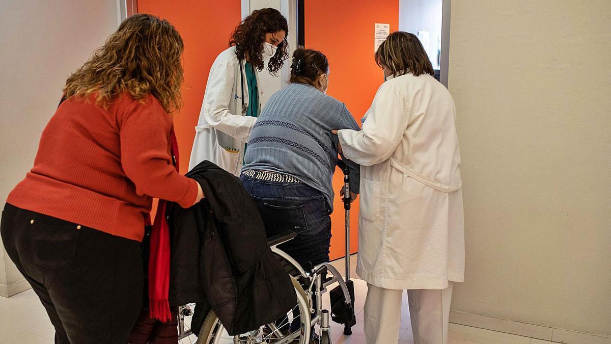 Lucía Fuentes y Lucía Pelaz ayudan a una paciente a entrar a su consulta. | Emilio Fraile