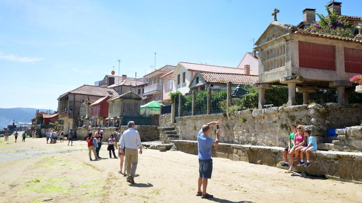 Visitantes contemplando los afamados hórreos. // G. Santos