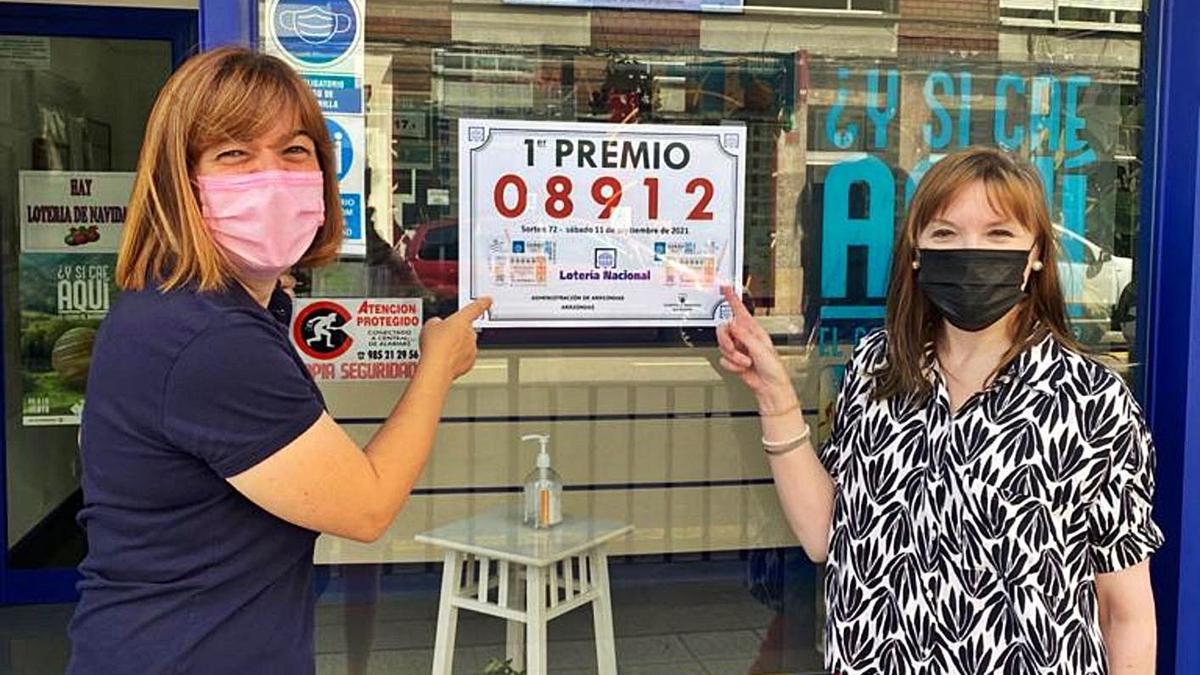 Claudia Intriago e Isabel González, ayer, a la puerta de su local, con el cartel del número premiado.