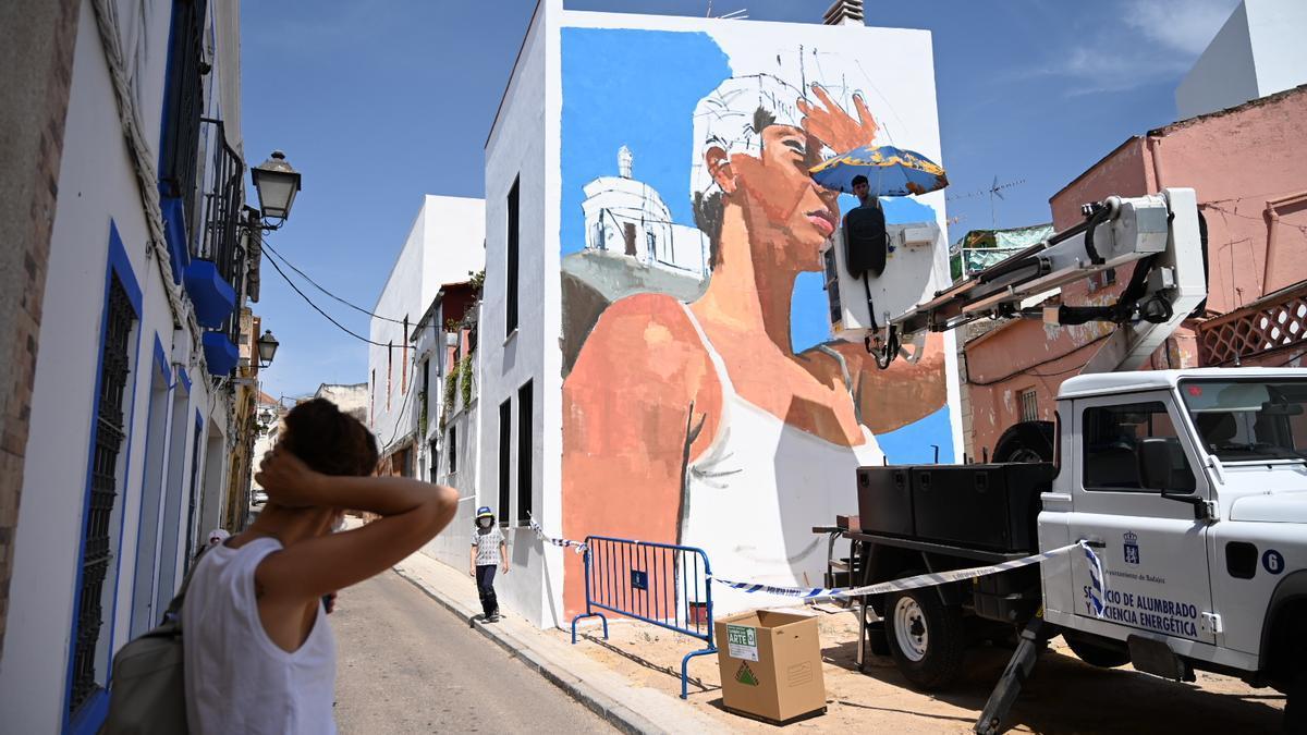 Miguel Tinoco en la grúa que está utilizando para pintar su mural.