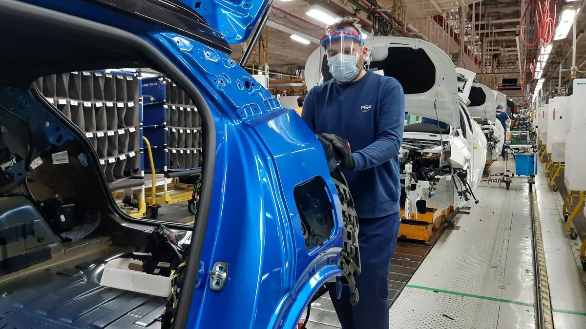 Un hombre trabaja en una fábrica de automóviles