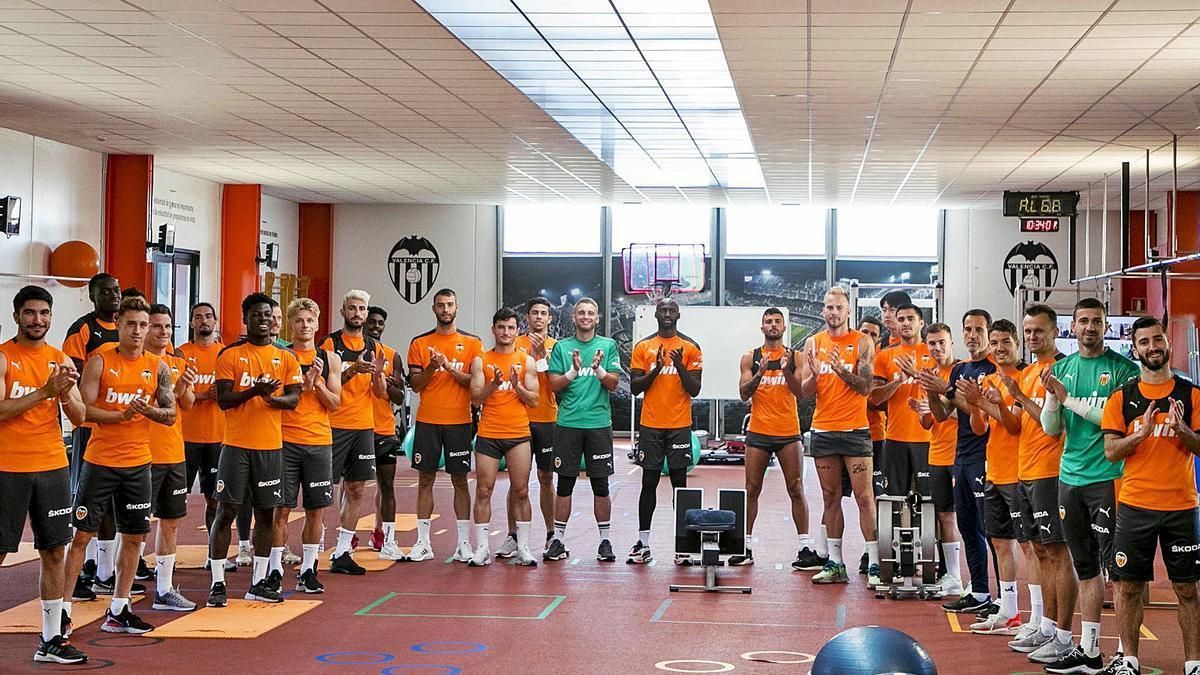 Los futbolistas del Valencia aplauden, en una acción de bienvenida a los aficionados que regresan a Mestalla.   LÁZARO DE LA PEÑA/VCF