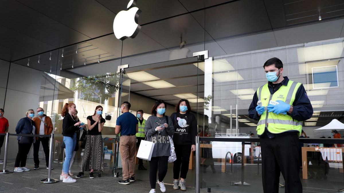 Varias personas con mascarilla esperan para entrar en una tienda de Apple.